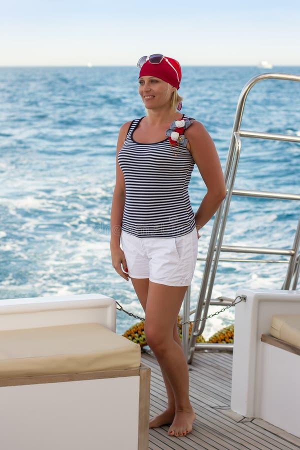 美丽的苗条同路人,俏丽的妇女站立在海游艇的船尾反对绿松石海 免版税库存照片