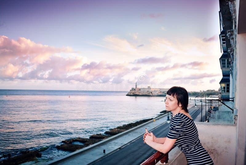 年轻美丽的苗条女孩低颈露肩的礼服阳台Malecon堤防El Morro堡垒哈瓦那古巴大西洋 免版税库存图片