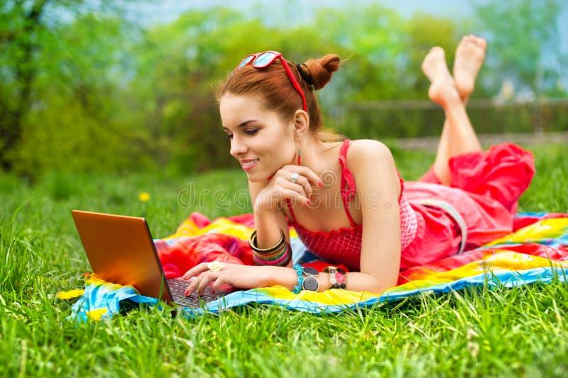 美丽的草膝上型计算机妇女 库存照片