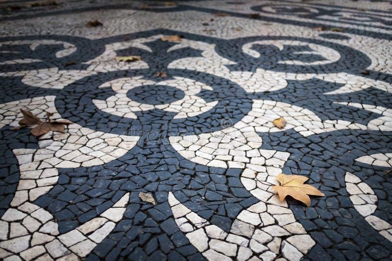 美丽的葡萄牙路面的细节在Liberdade大道的在市里斯本,葡萄牙,有干燥叶子的 免版税库存照片