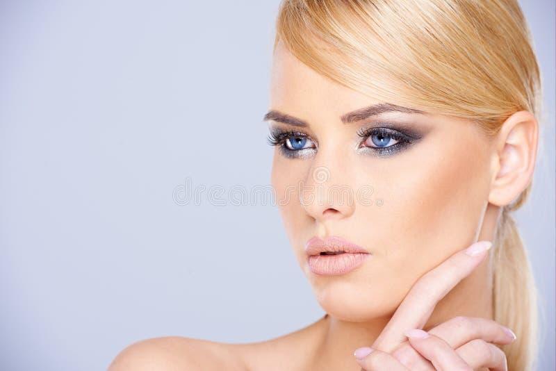 美丽的蓝眼睛的妇女佩带的构成 免版税库存照片