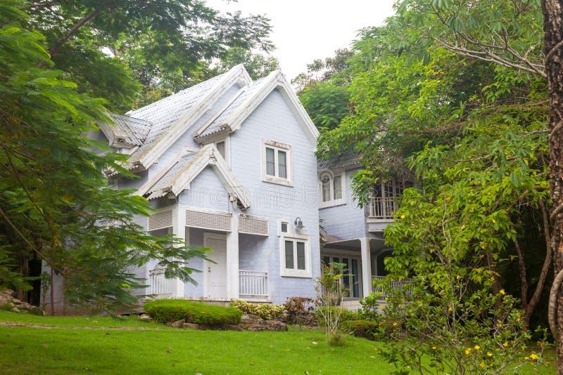 美丽的蓝色房子绿草和大树 免版税库存照片