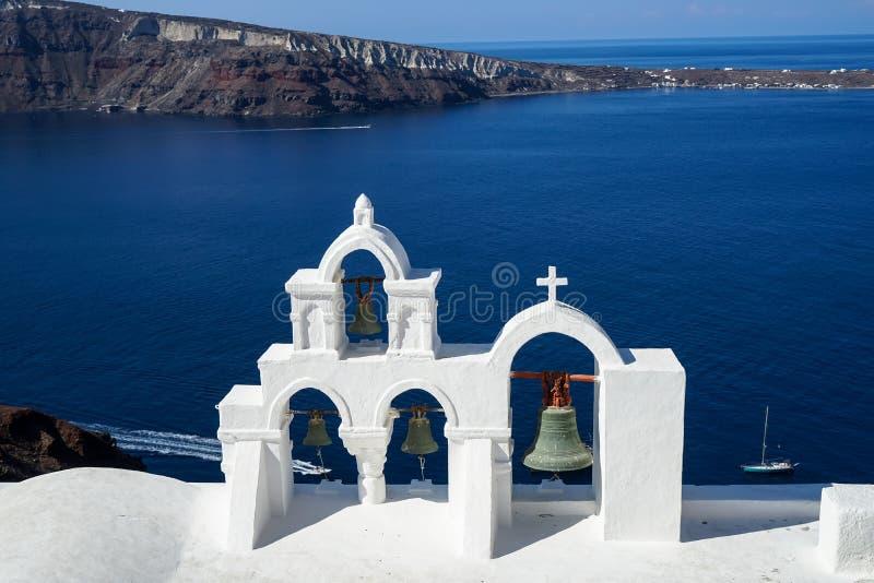 美丽的蓝色爱琴海全景,帆船和破火山口从Oia村庄有白色教会的顶房顶前景 免版税库存图片