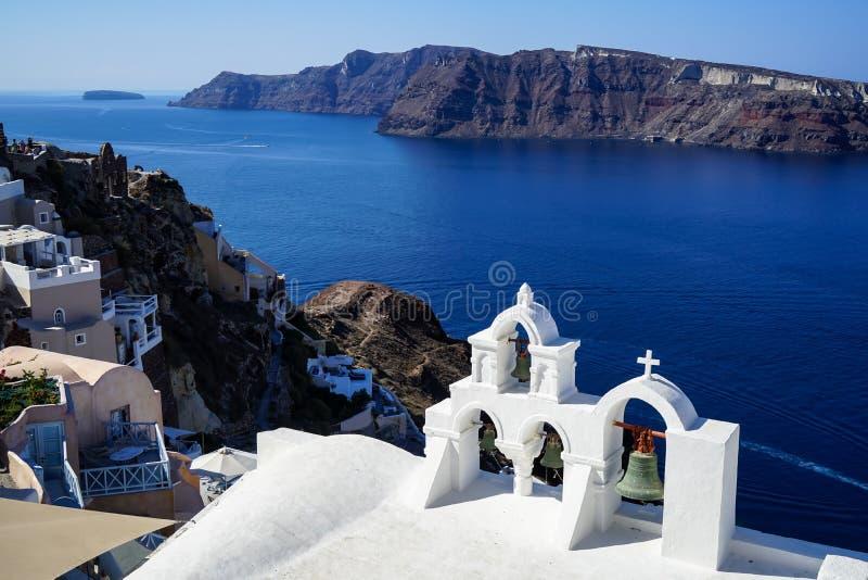 美丽的蓝色爱琴海和破火山口全景从Oia村庄有白色教会前景的,大厦沿海岛 免版税图库摄影