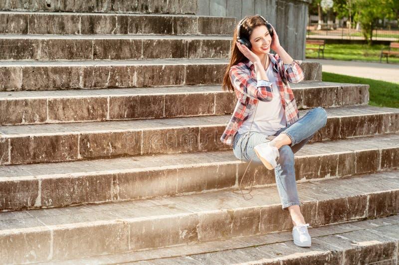 美丽的行家坐台阶在有耳机的城市公园 免版税库存照片