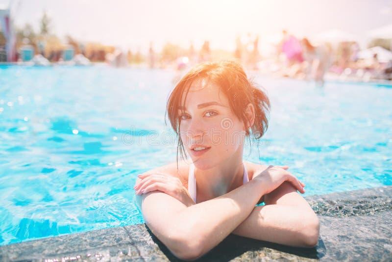 美丽的被晒黑的妇女画象放松在游泳池温泉的白色游泳衣的 热的夏日和明亮晴朗 免版税库存图片