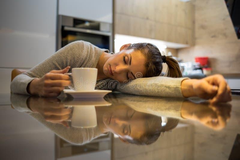 美丽的被用尽的年轻女人睡着了,当喝咖啡时 免版税库存照片