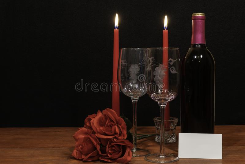 美丽的被铭刻的酒杯和瓶红酒、红色蜡烛和英国兰开斯特家族族徽在木桌上与名牌在黑暗的背景 库存图片