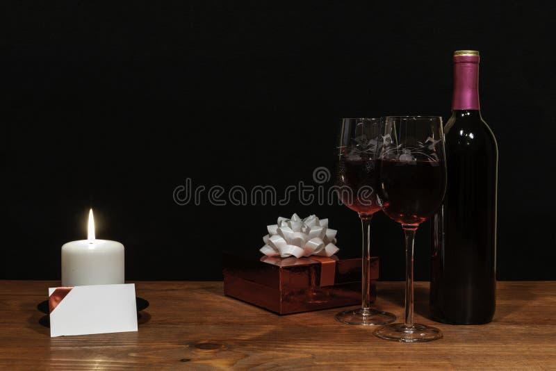 美丽的被铭刻的酒杯和瓶红酒,白色蜡烛,包裹了当前与在木桌上的弓与在黑暗的名牌 免版税图库摄影