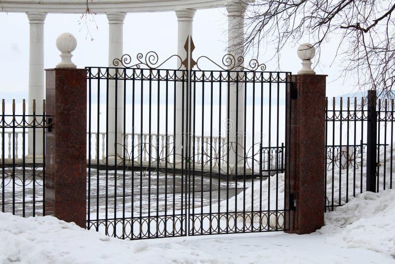 美丽的装饰生铁加工的篱芭的图象有艺术性的锻件的 冬天 图库摄影