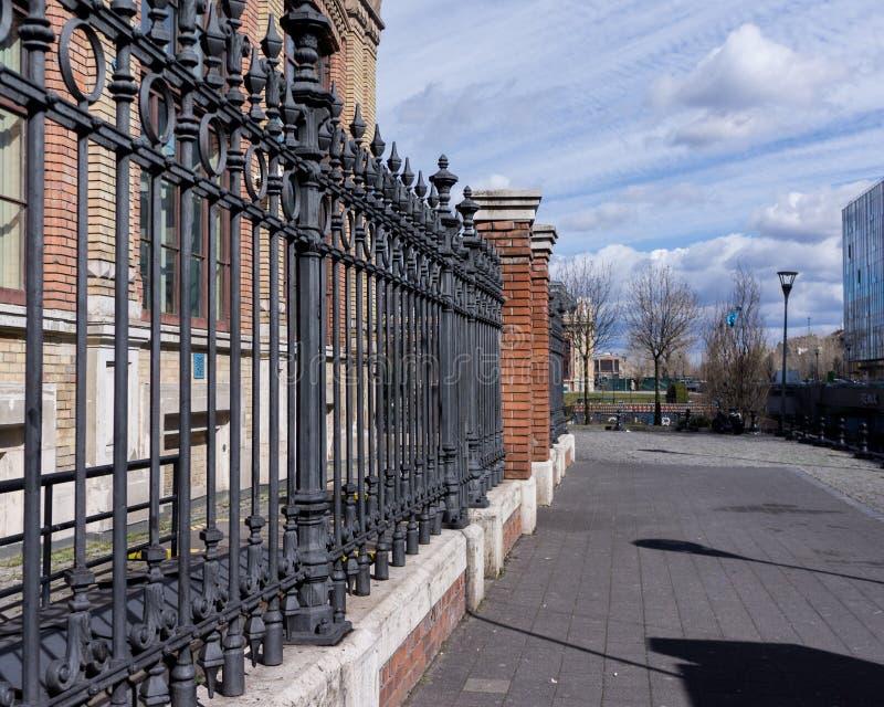 美丽的装饰生铁加工的篱芭的图象有艺术性的锻件的 金属栏杆关闭 免版税库存照片
