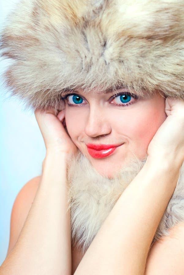 美丽的裘皮帽微笑的妇女 免版税库存图片