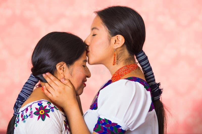 美丽的西班牙穿传统安地斯山的衣物的母亲和女儿,看见从面对的外形角度 库存图片
