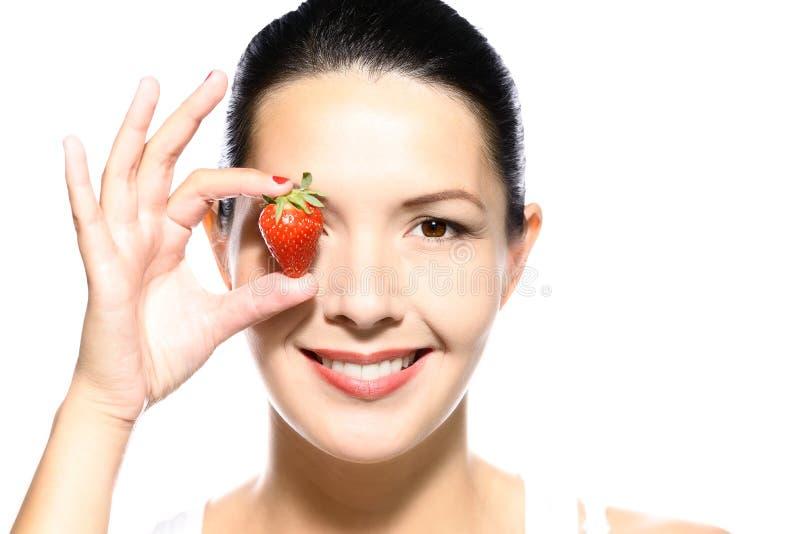 美丽的诱人的妇女用一个成熟草莓 免版税库存照片