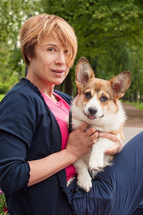 美丽的资深妇女拥抱她的狗宠物户外 免版税库存照片