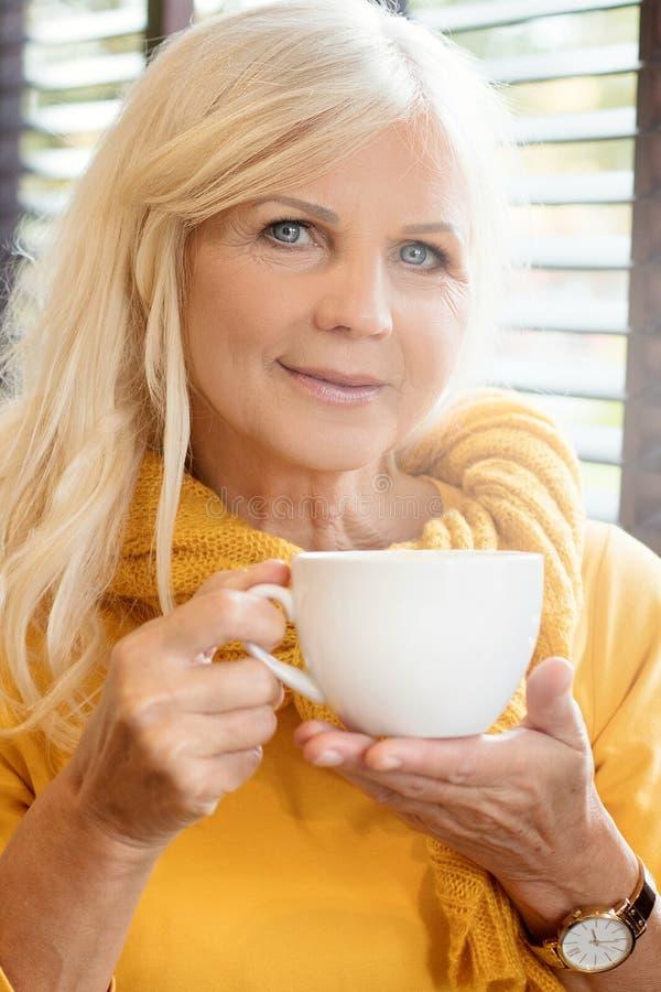 美丽的资深妇女饮用的cofee 库存图片