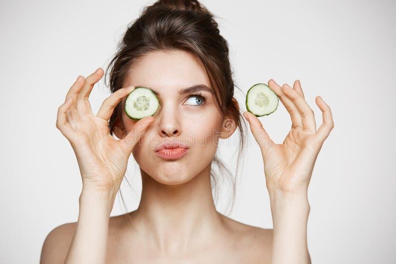 年轻美丽的赤裸在黄瓜切片后的女孩微笑的掩藏的眼睛在白色背景 秀丽温泉和整容术 库存照片