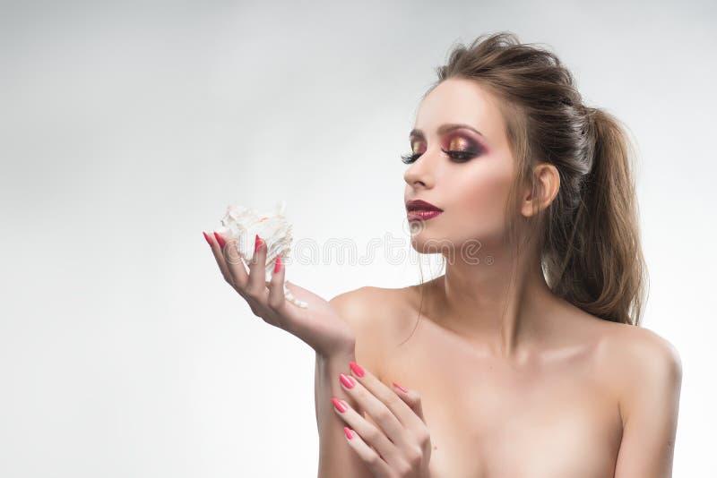 美丽的赤裸肩膀女孩在她的手上拿着一个贝壳 Hea 库存图片