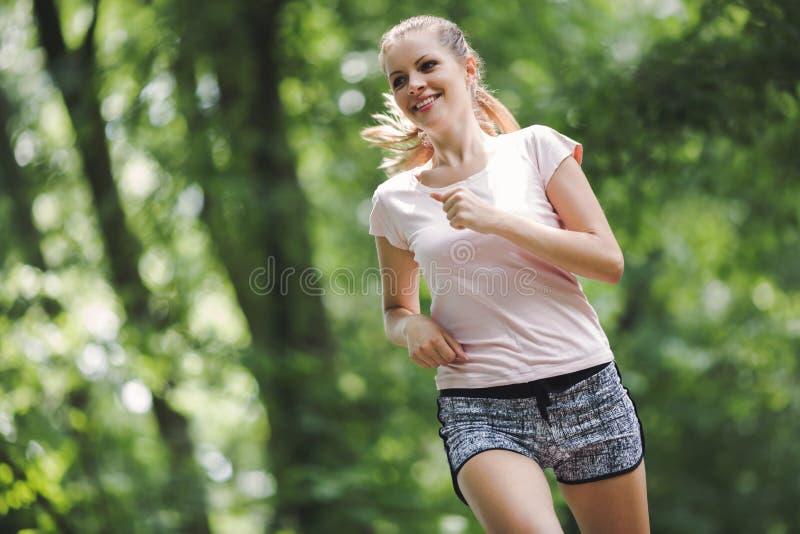 美丽的跑步的妇女本质上 免版税库存照片