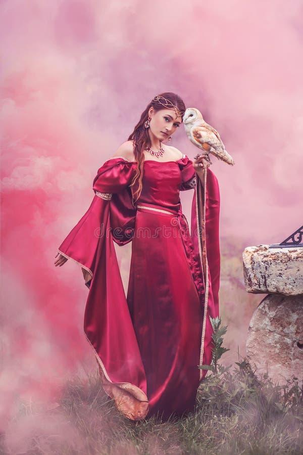 美丽的跳舞的妇女,女巫,有在她的手上的一头聪明的猫头鹰的 免版税图库摄影