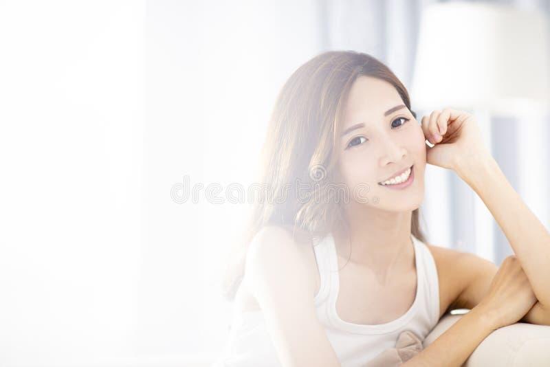 美丽的轻松的妇女坐沙发 库存照片