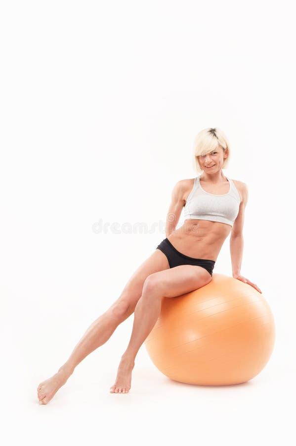 美丽的运动女孩坐fitball 图库摄影