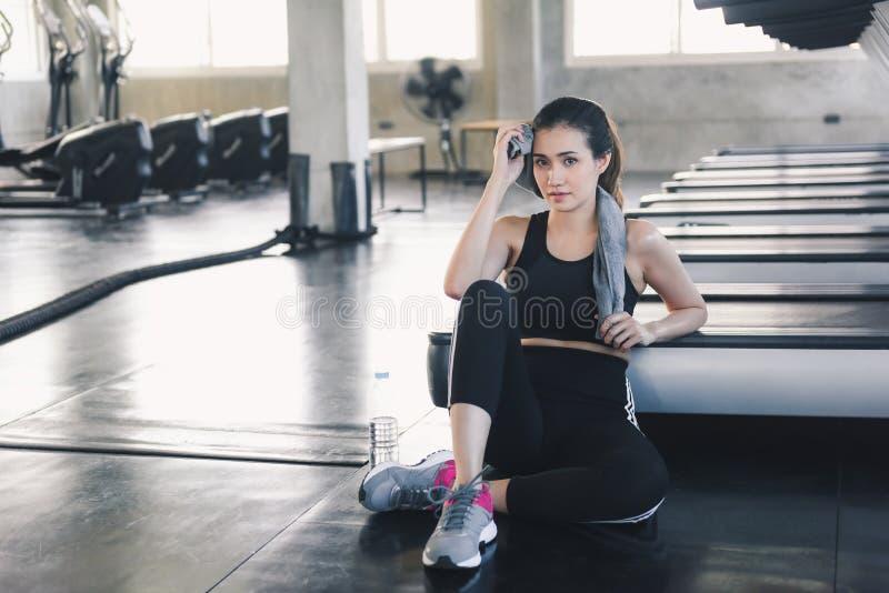 美丽的运动妇女在健身房,俏丽的女孩画象抹汗水与毛巾在行使以后运动服的行使  库存图片