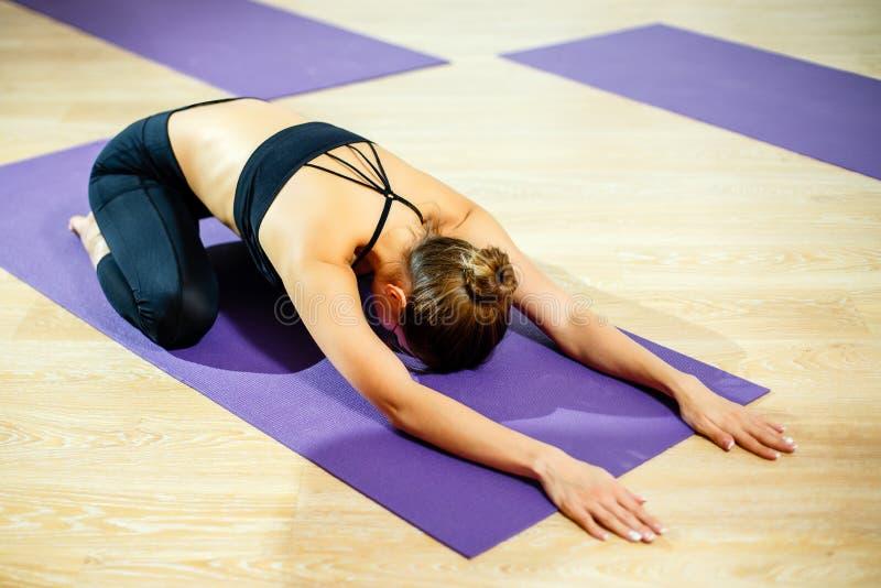 美丽的运动年轻女性做瑜伽Balasana 免版税库存图片