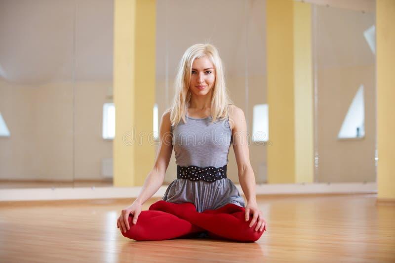 美丽的运动的适合信奉瑜伽者妇女在健身屋子实践瑜伽asana Padmasana -莲花姿势 免版税库存图片