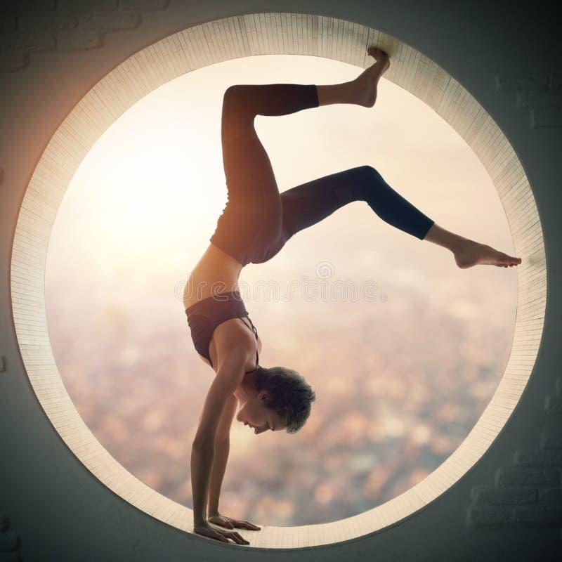 美丽的运动的适合信奉瑜伽者妇女在窗口里实践瑜伽手倒立asana Bhuja Vrischikasana -蝎子手倒立姿势 免版税库存图片