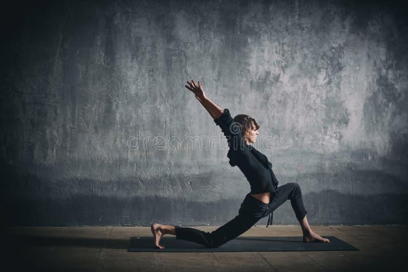 美丽的运动的适合yogini妇女在黑暗的大厅里实践瑜伽asana Virabhadrasana 1 -战士姿势1 免版税库存照片