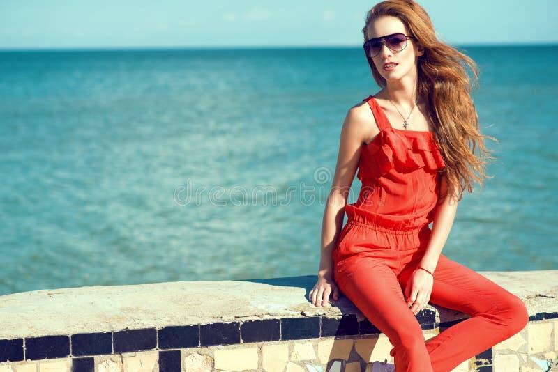 年轻美丽的迷人的时髦的妇女佩带的珊瑚红色连衫裤和黑暗的时髦太阳镜坐栏杆在海边 免版税库存照片