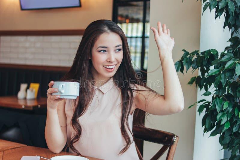 美丽的迷人的深色的长发微笑的亚裔女孩有早餐用咖啡在咖啡馆和挥动对朋友 库存图片
