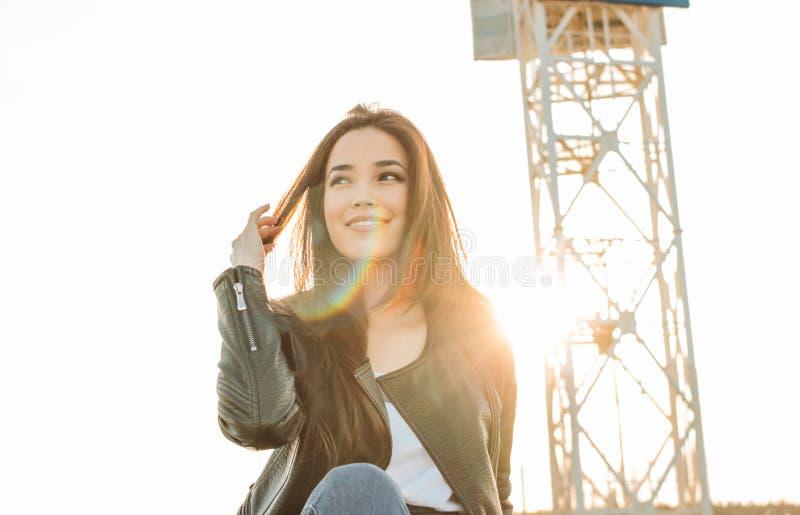 美丽的迷人的深色的黑皮夹克的长发愉快的亚裔女孩在日落 免版税图库摄影