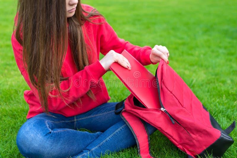 美丽的迷人的青少年的女孩包装的材料播种的特写镜头照片到被打开的书包里坐在里面的绿草草坪 图库摄影