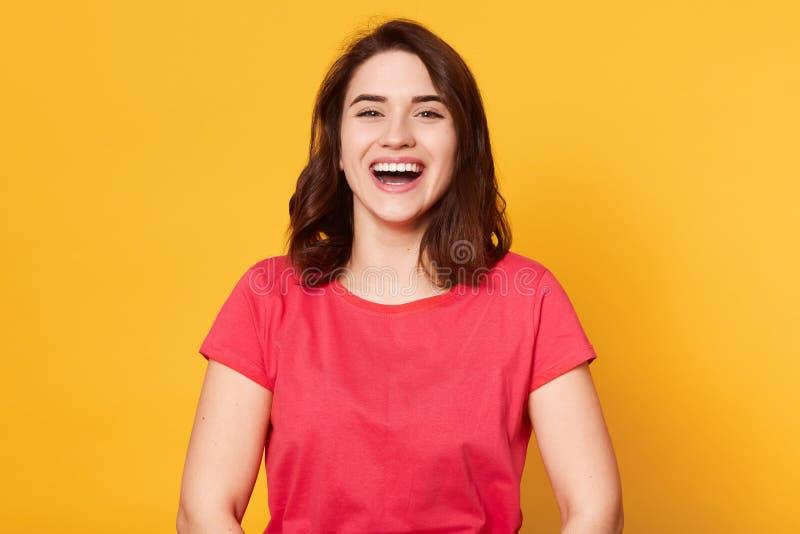 美丽的逗人喜爱的深色头发的女孩接近的画象穿偶然红色T恤杉的心情的,笑,享受高兴户内 免版税库存图片