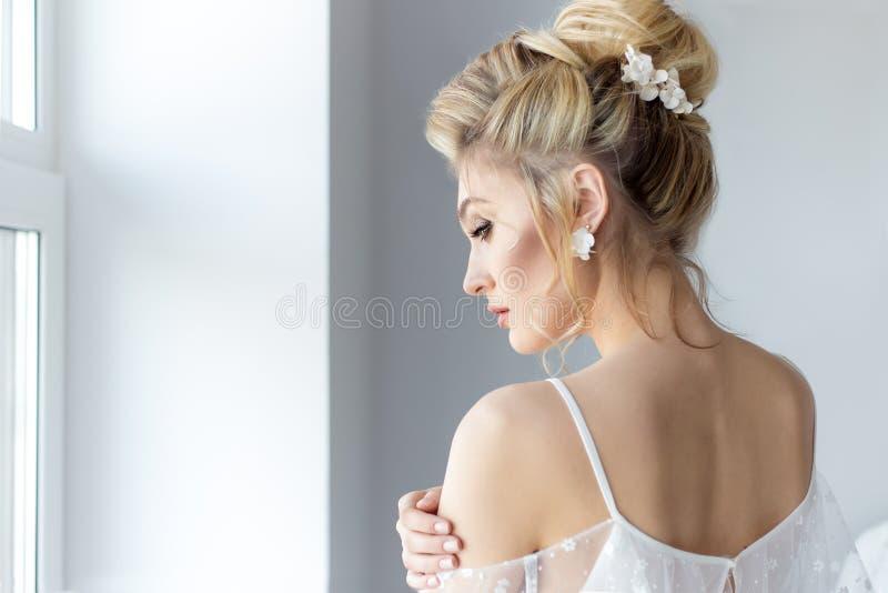 美丽的逗人喜爱的甜女孩在有明亮的构成smokey的轻的礼服美丽的闺房注视与hairsty一个美好的晚上 免版税库存图片