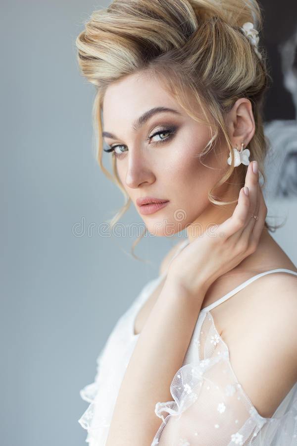 美丽的逗人喜爱的甜女孩在有明亮的构成smokey的轻的礼服美丽的闺房注视与hairsty一个美好的晚上 图库摄影