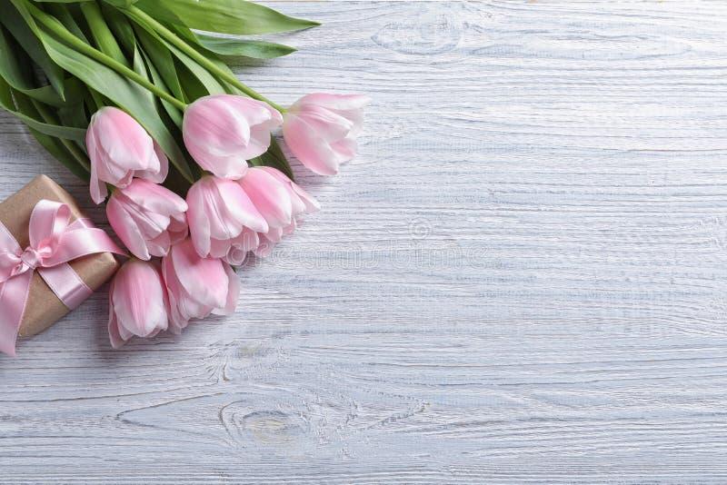 美丽的郁金香和礼物盒为母亲在木背景的` s天, 库存照片