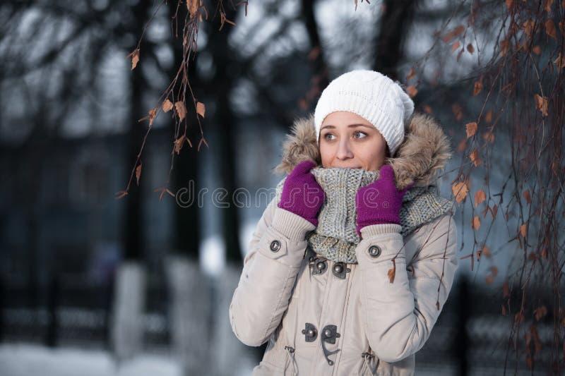 美丽的金发女孩我冬天给在雪背景的.attractive微笑的妇女纵向穿衣 一个时兴的模型的感情画象在白色站立在的外套和贝雷帽的 免版税图库摄影