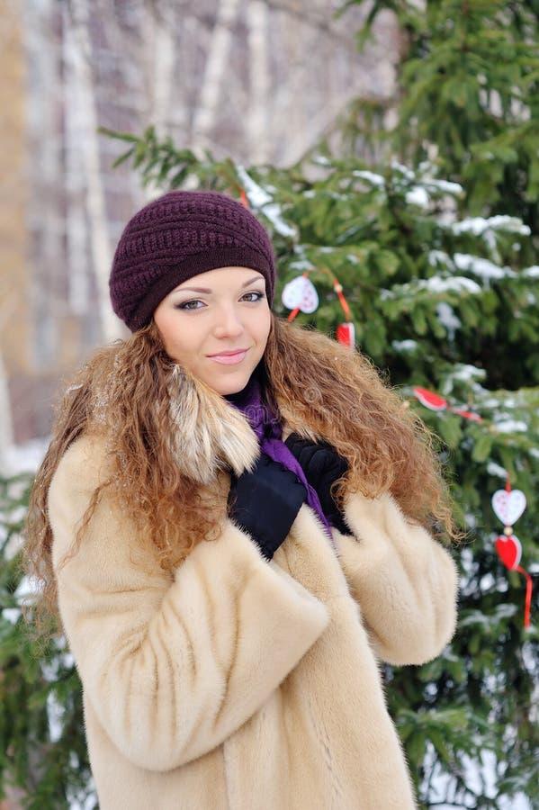 美丽的金发女孩我冬天给在雪背景的.attractive微笑的妇女纵向穿衣 库存照片
