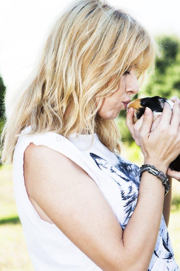美丽的金发妇女亲吻的逗人喜爱的宠物兔宝宝 库存图片