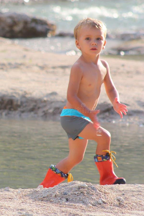 美丽的金发小男孩在河使用 免版税图库摄影