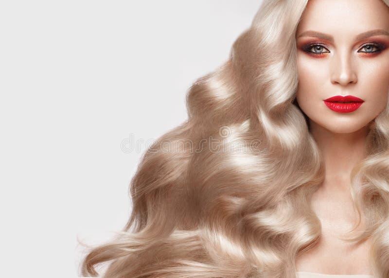 美丽的金发碧眼的女人以与卷毛、自然构成和红色嘴唇的好莱坞方式 秀丽表面和头发 免版税库存图片
