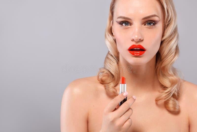 美丽的金发碧眼的女人以与卷毛,红色嘴唇,唇膏的好莱坞方式在手中 秀丽表面和头发 整容术 免版税库存图片