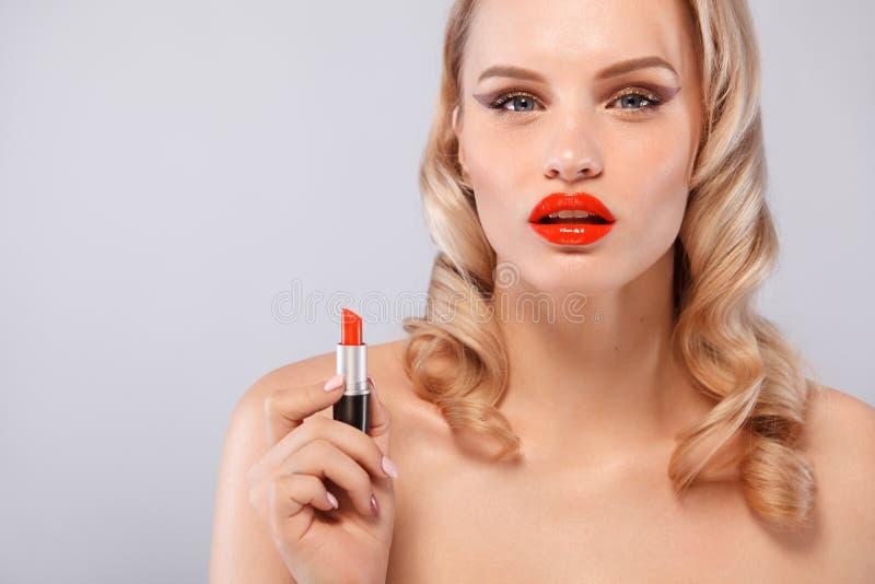 美丽的金发碧眼的女人以与卷毛,红色嘴唇,唇膏的好莱坞方式在手中 秀丽表面和头发 整容术 免版税库存照片