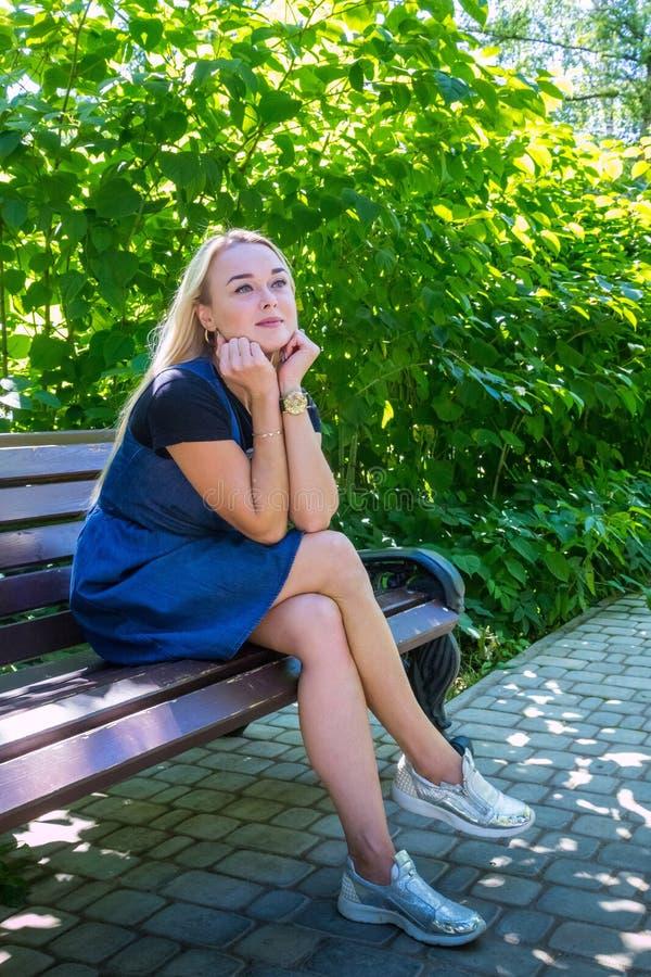 美丽的金发碧眼的女人在公园 走在一夏天好日子的年轻俏丽的白种人妇女 免版税库存图片