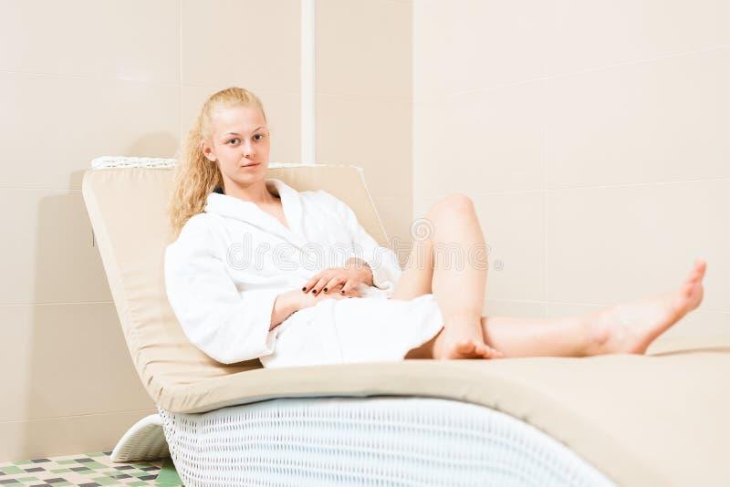 美丽的金发碧眼的女人在温泉沙龙放松 在在沙发的一件白色长袍的迷人的少女 库存照片
