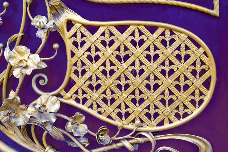美丽的金玫瑰由金属制成 伪造,以其他金属制品为背景 免版税库存照片