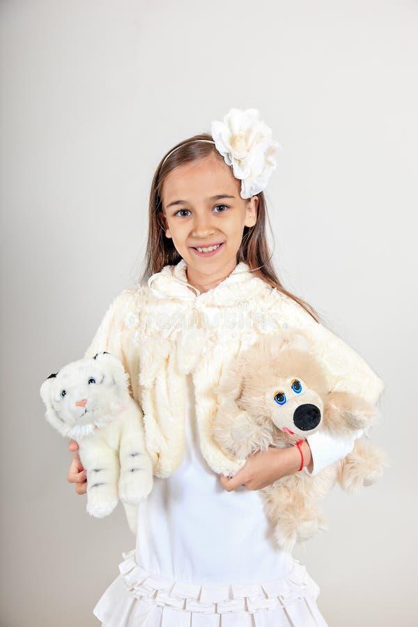 美丽的长发女孩在一件白色外套穿戴了 孩子拿着在被隔绝的灰色背景的软的玩具 库存照片